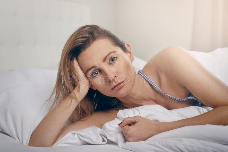 Mensonge blond d'une cinquantaine d'années attrayant de femme étayé dans le lit image libre de droits