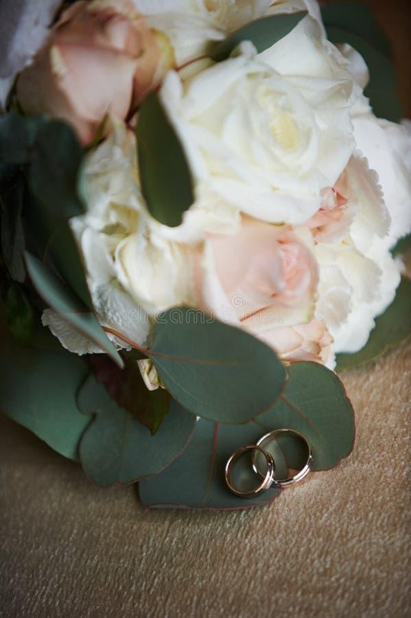 Mensonge d'anneaux de mariage à côté de bouquet de mariage image stock