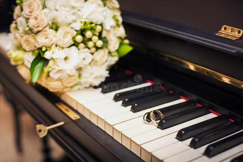Mensonge d'anneaux de mariage d'or sur le piano photos stock