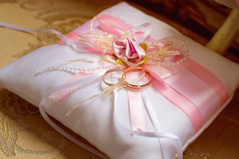 Mensonge d'anneaux de mariage d'or sur un oreiller en soie décoratif avec les rubans roses de satin images libres de droits