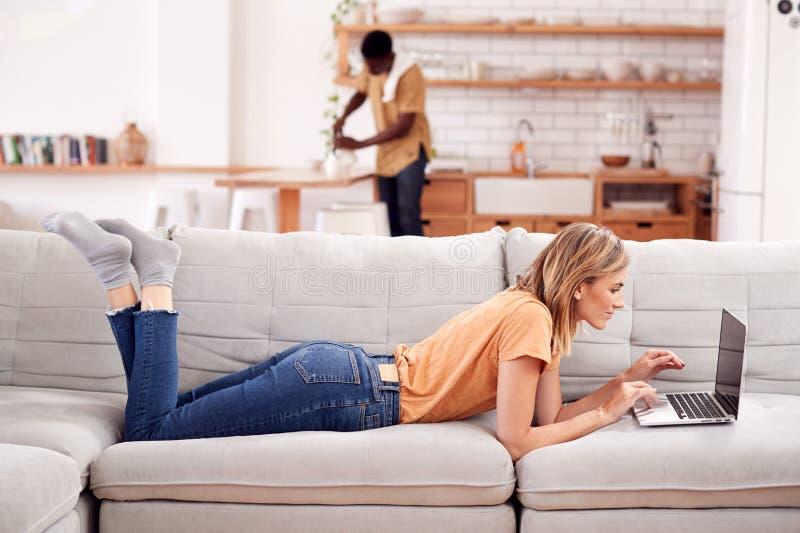 Mensonge de détente de femme sur l'ordinateur de Sofa At Home Using Laptop avec l'homme dans la cuisine derrière images stock