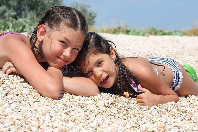 Mensonge de deux filles sur la plage photographie stock