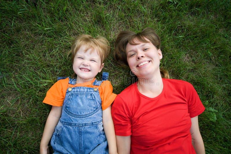 Mensonge de femme et d'enfant sur l'herbe verte photo stock
