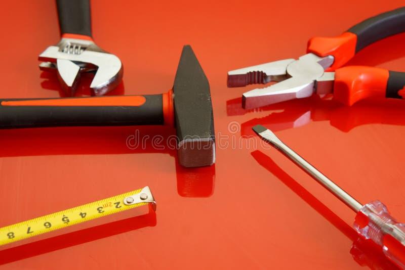 Mensonge de pinces, de ruban métrique, de tournevis, de marteau et de clé réglable sur une surface polie rouge images stock