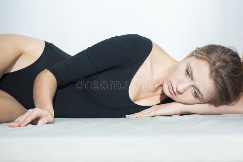 Mensonge de port de femme triste sur le plancher photographie stock libre de droits