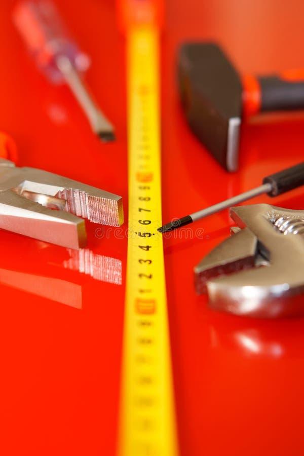 Mensonge de tournevis, de pinces, de ruban métrique, de marteau et de clé réglable sur une surface polie rouge Outils pour le méc image stock