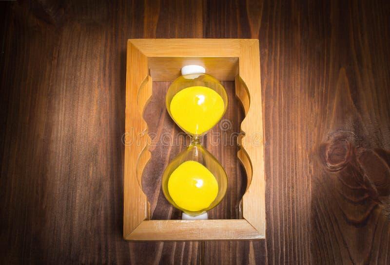 Mensonge en verre d'horloge de rétro sable en bois de côté avec le sable sur le fond en bois concept d'arrêt de temps images stock