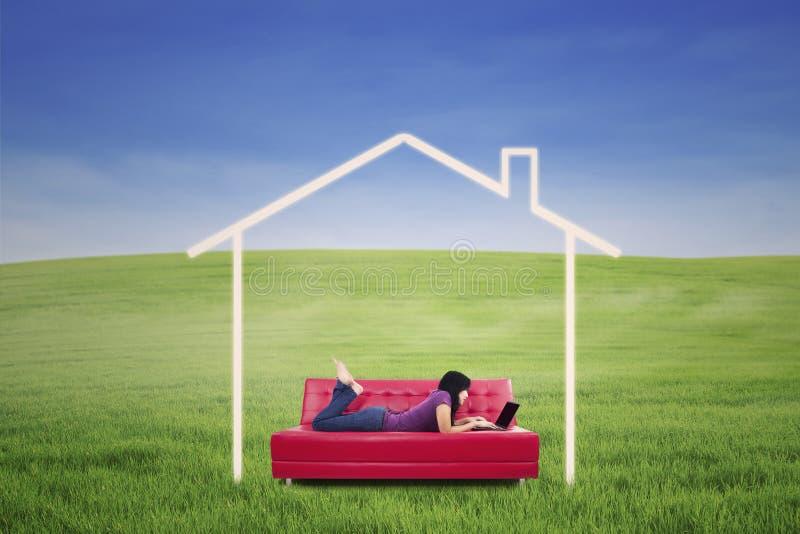 Mensonge femelle asiatique sur le sofa dans la maison rêveuse extérieure photo stock
