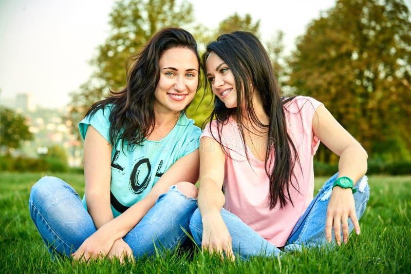Mensonge heureux de deux jeune filles sur l'herbe photographie stock libre de droits