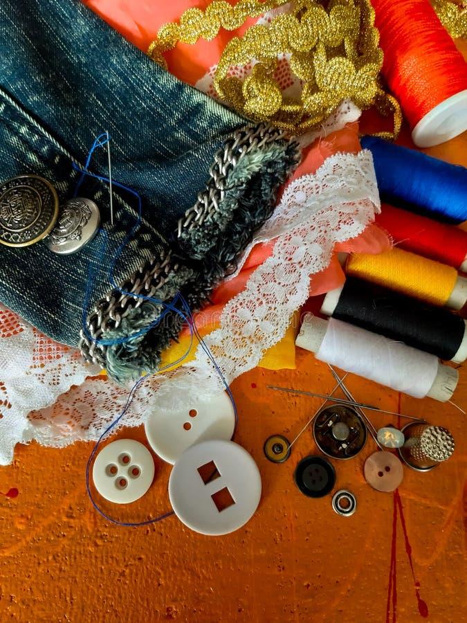 Mensonge sur un fond orange - boutons, fils, aiguilles, dentelle, photos stock