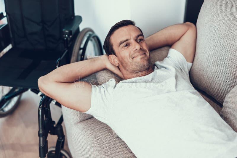 Mensonges beaux de sourire d'homme sur Sofa Near Wheelchair photographie stock libre de droits