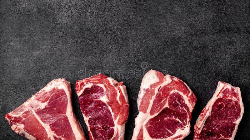 Mensonges crus de bifteck de viande sur le fond noir Vue supérieure photos stock