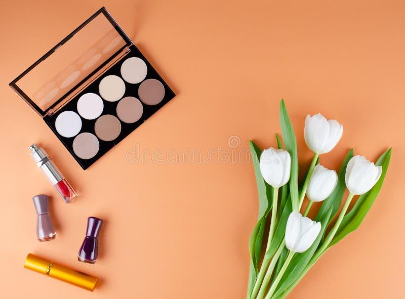 Mensonges de cosmétiques et de fleurs sur un fond mou de pêche Contenu du sac cosmétique des femmes photo libre de droits