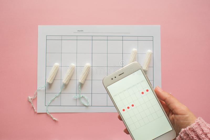 Menstrual cycle. Calendar for the month with marks and a mobile application on the smartphone screen. royalty free stock image