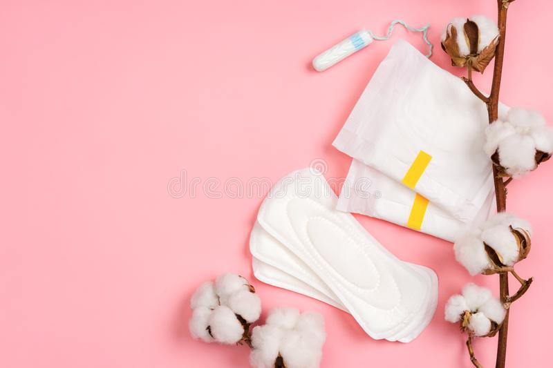 Menstrual napkins and tampons with cotton flowers on pink background. stock photography