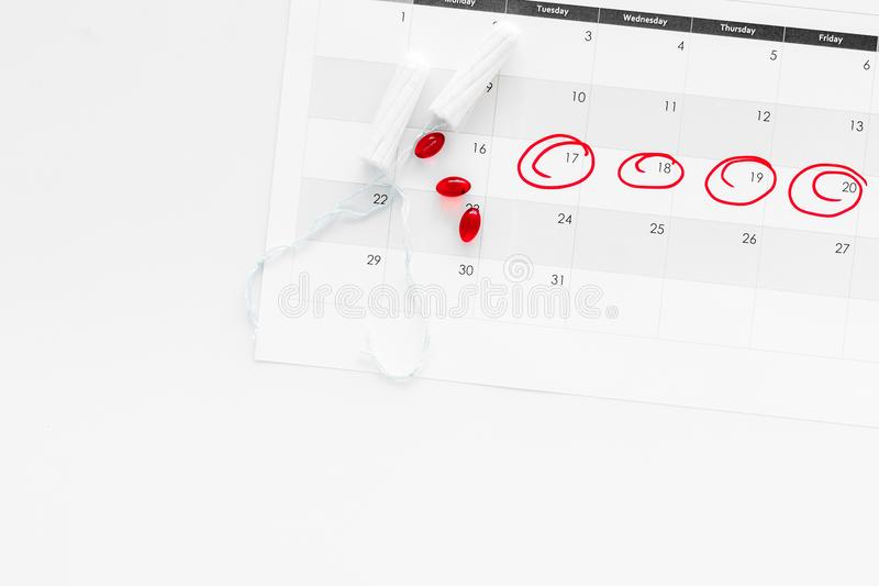 Menstrual period concept. Menstruation calendar with hygienic tampon on white background top view copy space royalty free stock image