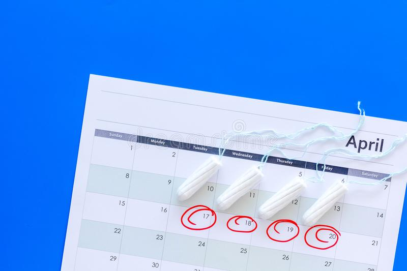 Menstrual period concept. Menstruation calendar with hygienic tampons on blue background top view space for text royalty free stock photo