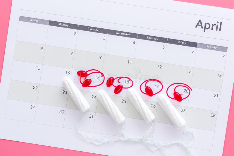 Menstrual period concept. Menstruation calendar with hygienic tampons and pills on pink background top view royalty free stock images