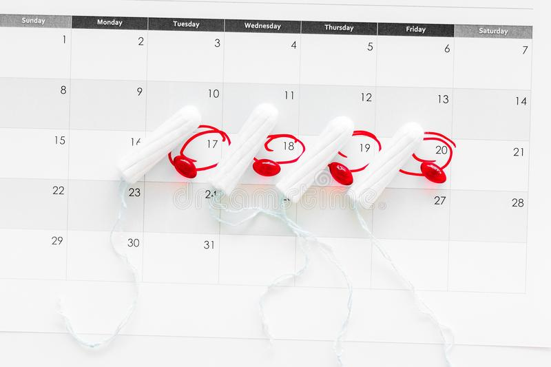 Menstrual period concept. Menstruation calendar with hygienic tampons and pills on white background top view royalty free stock photography