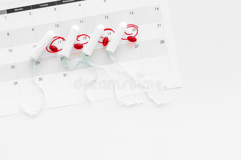 Menstrual period concept. Menstruation calendar with hygienic tampons and pills on white background top view space for stock image