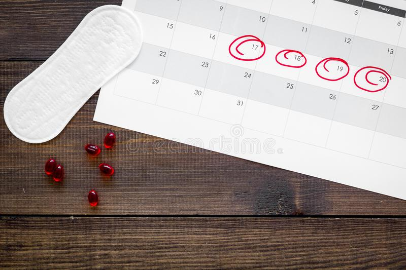 Menstrual period concept. Menstruation calendar with sanitary pads on dark wooden background top view copy space stock photography