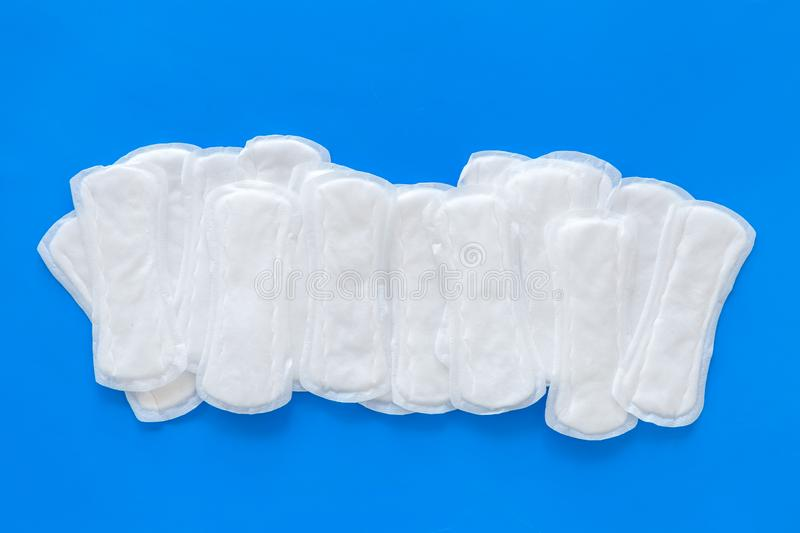 Menstrual period concept with sanitary pads on blue background top view stock images