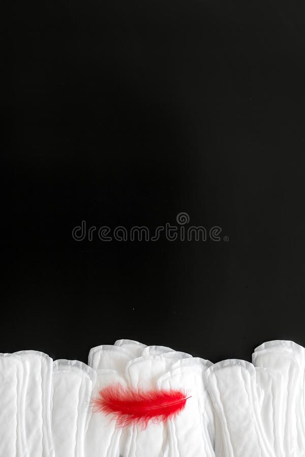 Menstrual period concept with sanitary pads and red feather on black background top view mock-up stock images