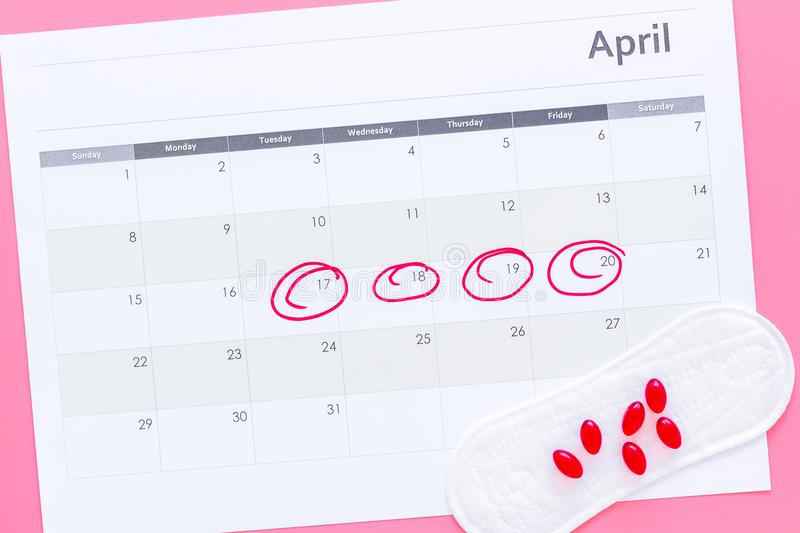 Menstruation cycle concept. Menstruation calendar with sanitary pads and contraceptive pills on pink background top view stock photo