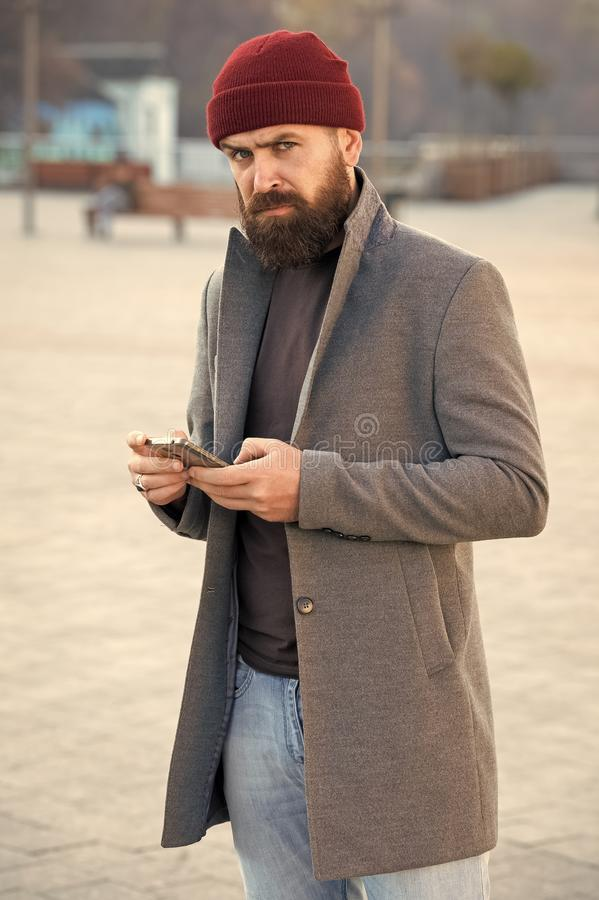 Menswear and male fashion concept. Man bearded hipster stylish fashionable coat and hat. Stylish modern outfit hat. Bright accessory. Hipster outfit. Stylish stock image