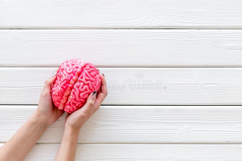Mental health concept with brain in hands on white wooden background top view copyspace. Brain functions. Mental health concept with brain in hands on white royalty free stock images
