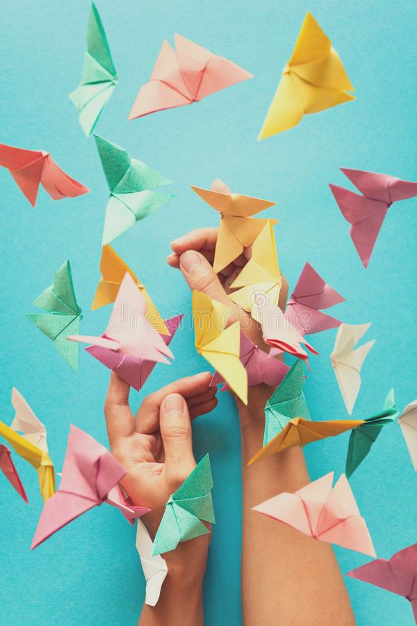 Mental health concept. Colorful paper butterflies flying and sitting on woman`s hands. Harmony emotion. Origami. Paper cut style. Toned stock photos