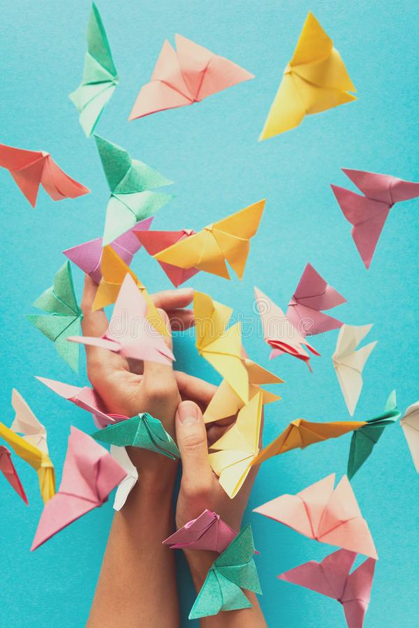 Mental health concept. Colorful paper butterflies flying and sitting on woman`s hands. Harmony emotion. Origami. Paper cut style. Toned stock image