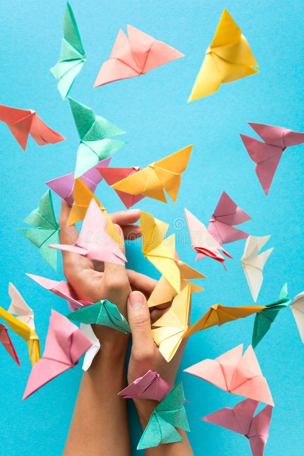 Mental health concept. Colorful paper butterflies flying and sitting on woman`s hands. Harmony emotion. Origami. Paper cut style.  stock photos