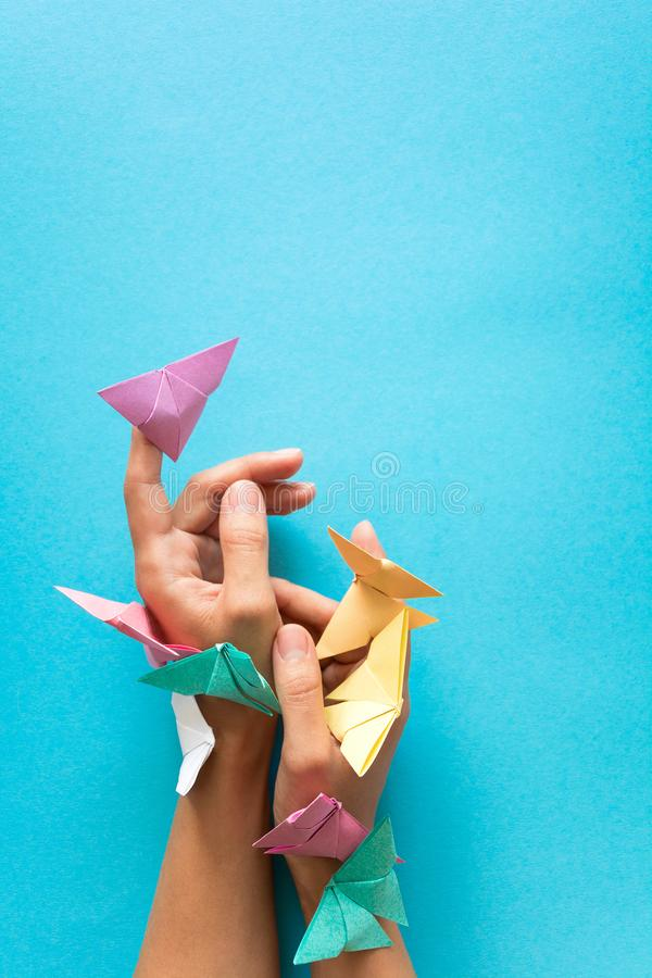 Mental health concept. Colorful paper butterflies flying and sitting on woman`s hands. Harmony emotion. Origami. Paper cut style.  stock images