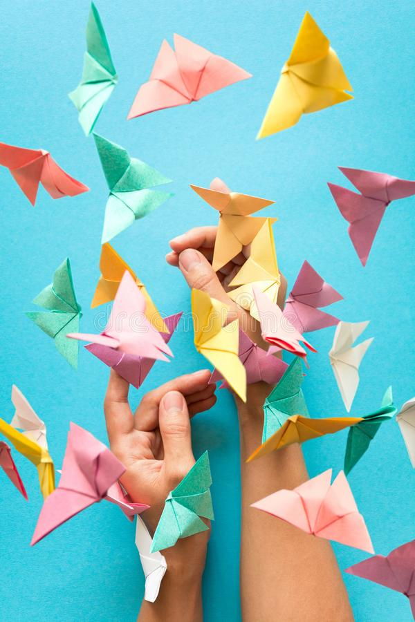 Mental health concept. Colorful paper butterflies flying and sitting on woman`s hands. Harmony emotion. Origami. Paper cut style.  royalty free stock photos
