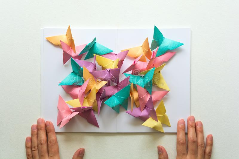 Mental health concept. Colorful paper butterflies sitting on book in shape of butterfly. Harmony emotion. Origami. Paper cut style.  royalty free stock image