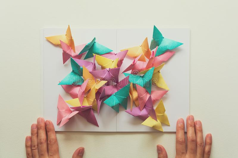 Mental health concept. Colorful paper butterflies sitting on book in shape of butterfly. Harmony emotion. Origami. Paper cut style. Toned royalty free stock photos