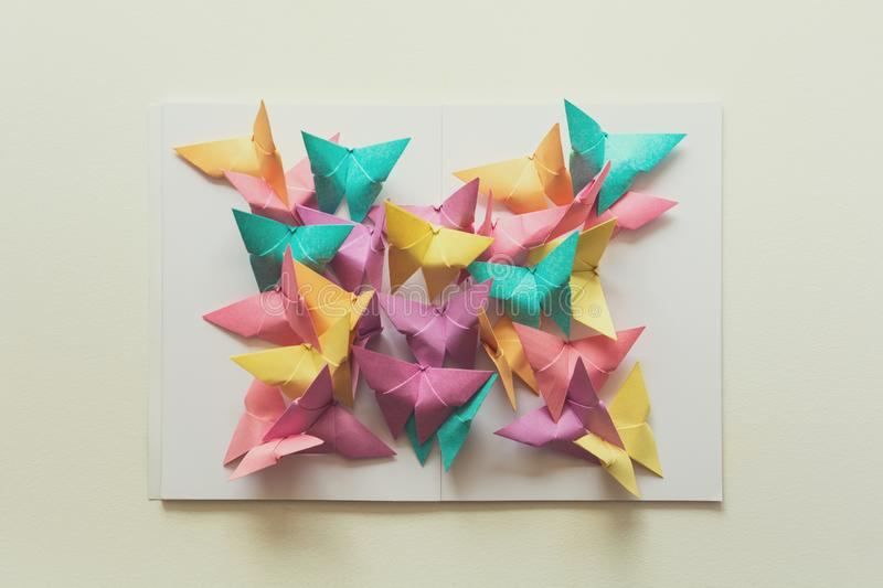 Mental health concept. Colorful paper butterflies sitting on book in shape of butterfly. Harmony emotion. Origami. Paper cut style. Toned stock photo