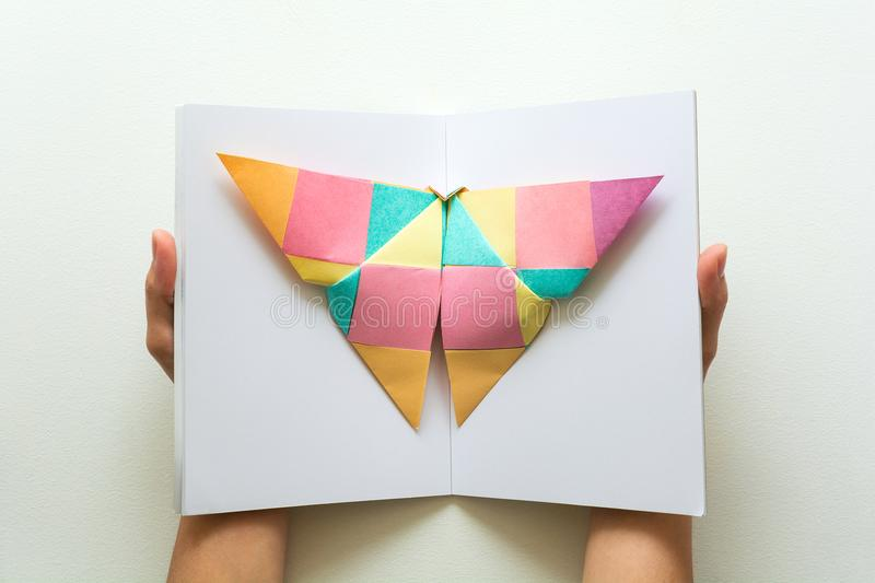 Mental health concept. Colorful paper butterfly sitting on book. Harmony emotion. Origami. Paper cut style stock photo
