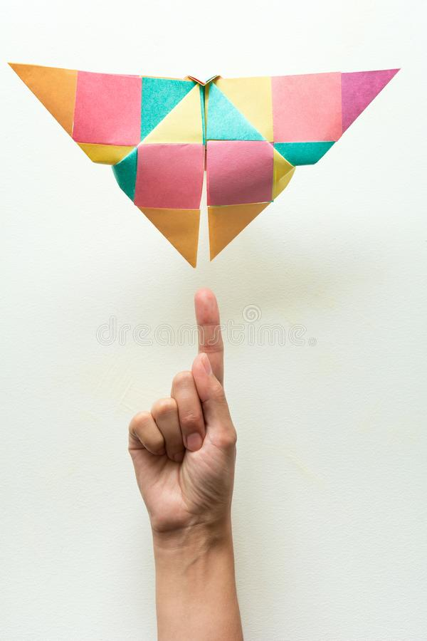 Mental health concept. Hand indicating on colorful paper butterfly. Harmony emotion. Origami. Paper cut style.  royalty free stock images