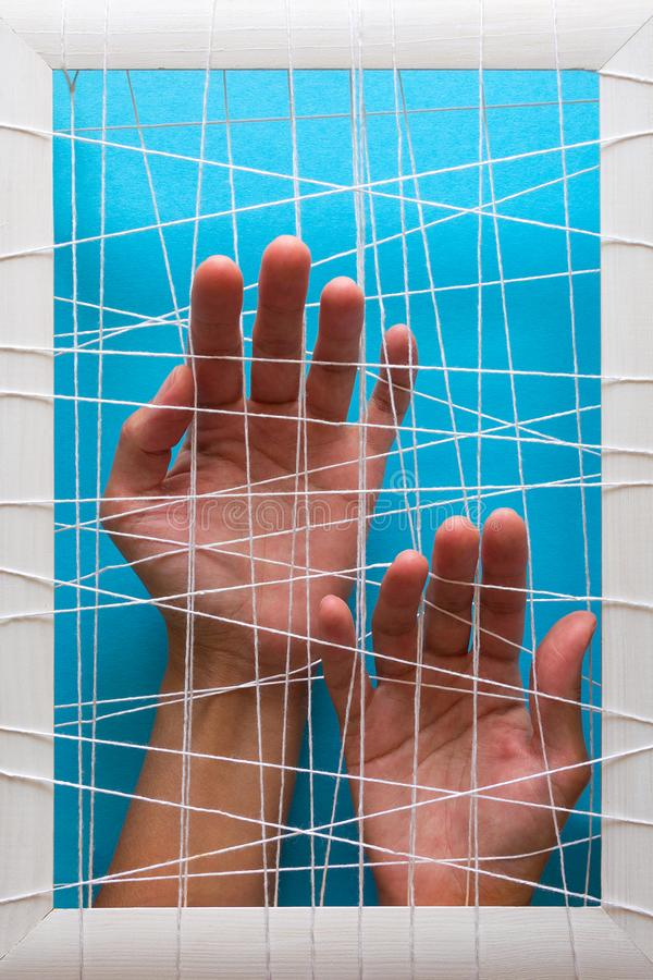 Mental health concept. Women`s hands try to break the fetters on blue background.  royalty free stock images