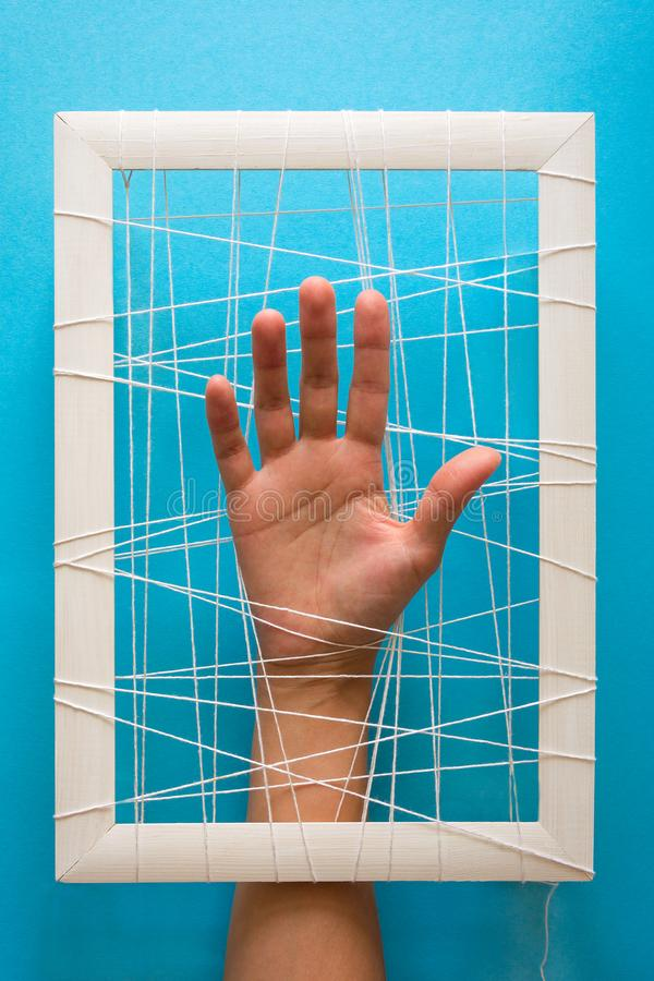 Mental health concept. Women`s hands try to break the fetters on blue background.  royalty free stock photo
