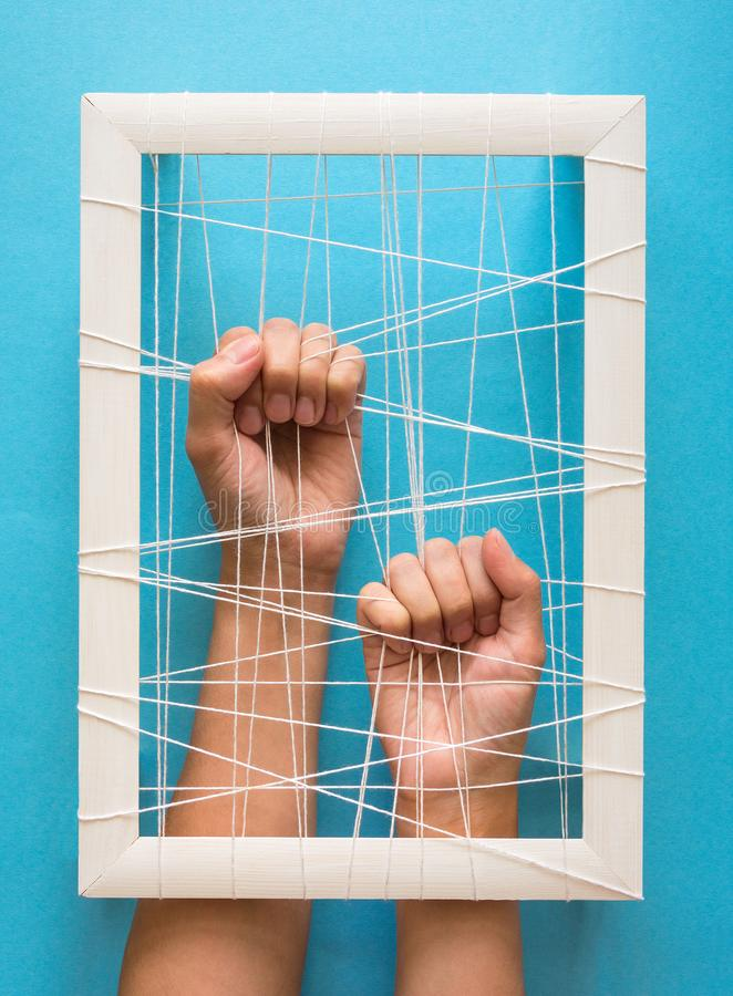 Mental health concept. Women`s hands try to break the fetters on blue background.  stock photography