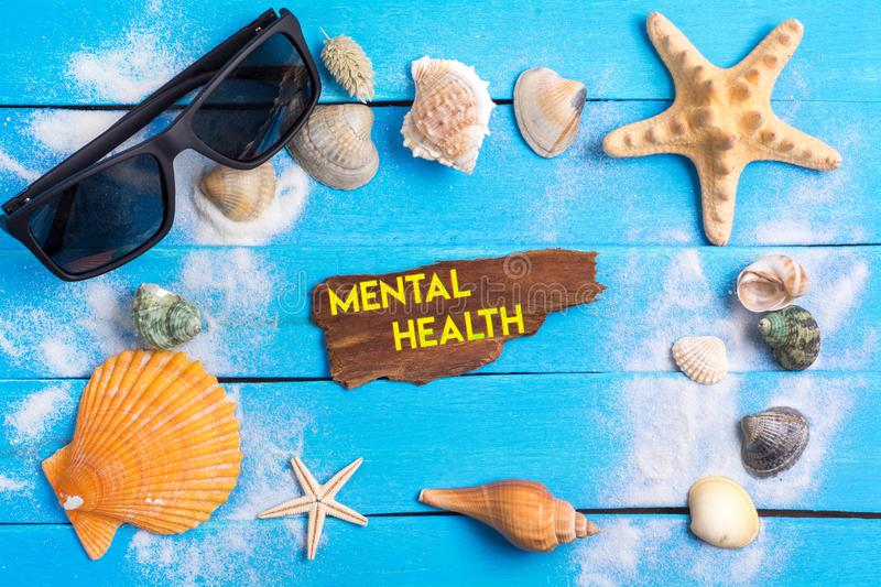 Mental health text with summer settings concept. Mental health text On Beach Accessories With Few Marine Items On Blue Wooden Plank , Summer concept royalty free stock image