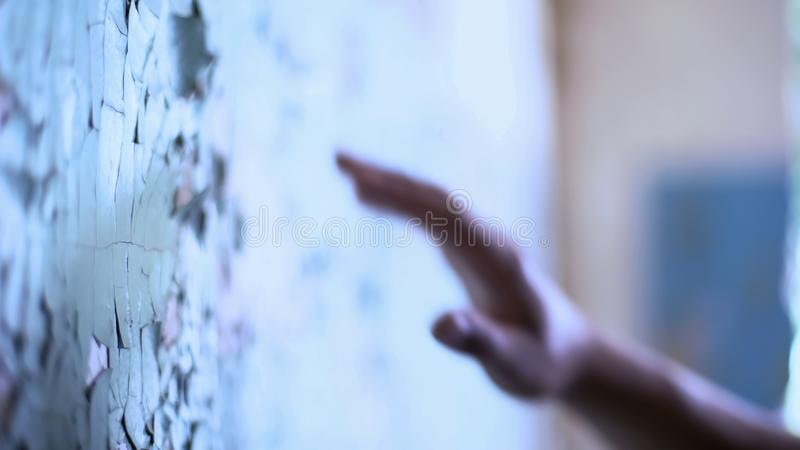 Mental house patient touching cracked wall, life difficulties concept, disease. Stock photo stock image
