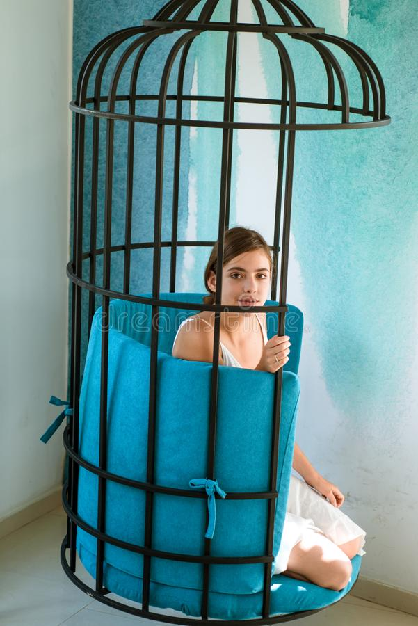 Mental mind. prisoner woman in cage - home confinement. freedom of cute girl in cage chair. fashion slave in captivity stock photography