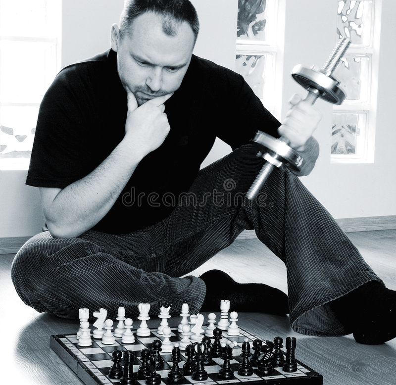 Mental and physical strength. Concept. Multitasking man playing chess and lifting dumbell