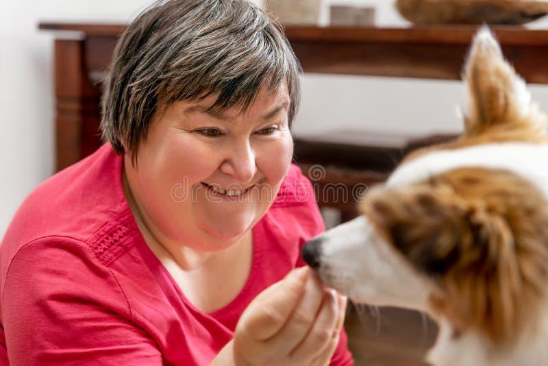 Mentalement - la femme handicapée alimente un chien images stock