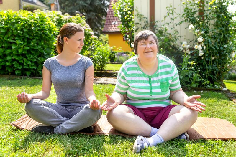 Mentally disabled woman and coach is doing yoga exercises. Two women, one of them a fitness or yoga coach, are doing some yoga or relaxation exercises, on women stock photo