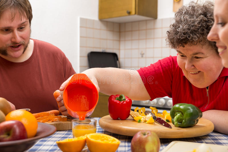 Mentally disabled woman and two caretakers cooking together. A mentally disabled women and two caretakers cooking together royalty free stock photography